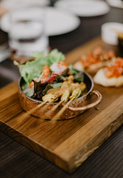 From above of delicious grilled meat on skewers served with salad in metal bowl placed on rustic wooden cutting board near sandwiches from white bread