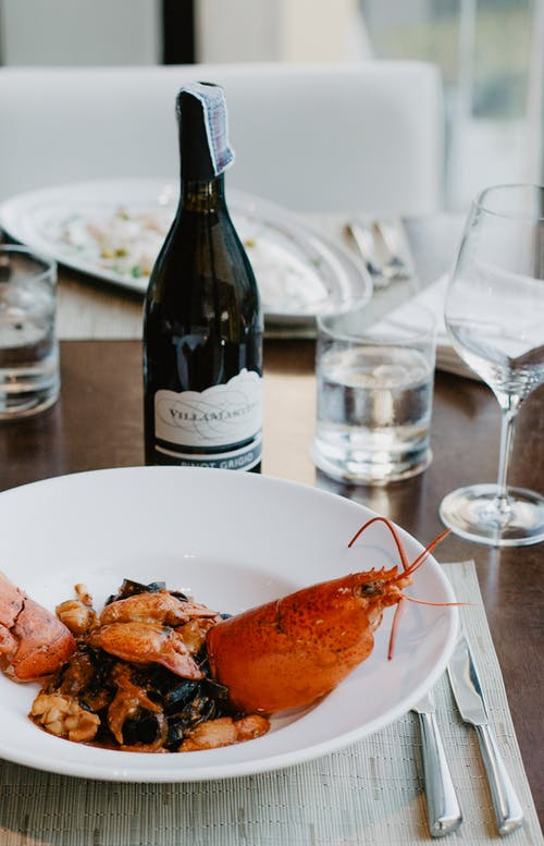 From above of plate with delicious dish from lobster served with bottle of wine placed on wooden table near glass of water and wineglass in restaurant