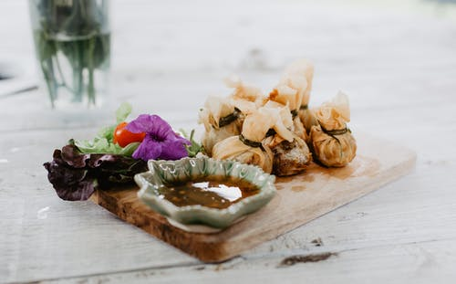 Dim sum and vegetables on wooden board in cafe
