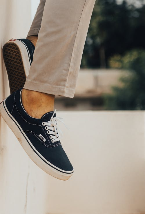 Side view of unrecognizable ethnic person in formal beige pants and black sneakers with white laces resting in city on blurred background