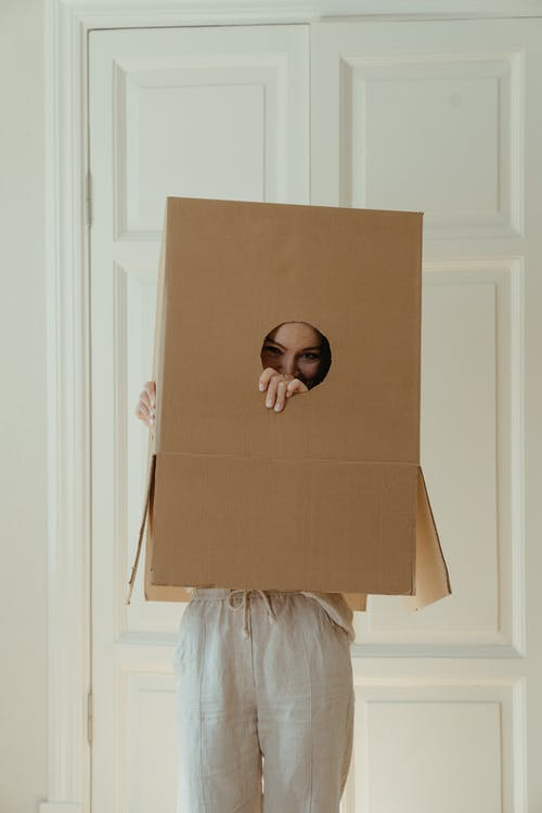 Girl in White Dress Holding Brown Cardboard Box