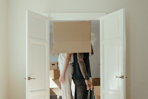 Person in Blue Denim Jeans Holding Brown Cardboard Box