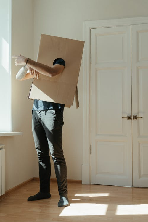 Woman in White Shirt and Blue Denim Jeans Holding Brown Cardboard Box