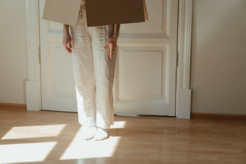 Person in White Pants and White Shoes Standing on Brown Wooden Floor
