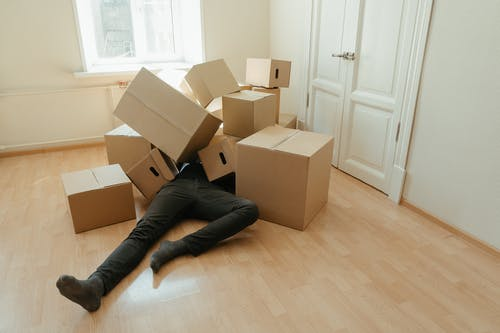 Person in Black Pants Lying on Brown Cardboard Boxes
