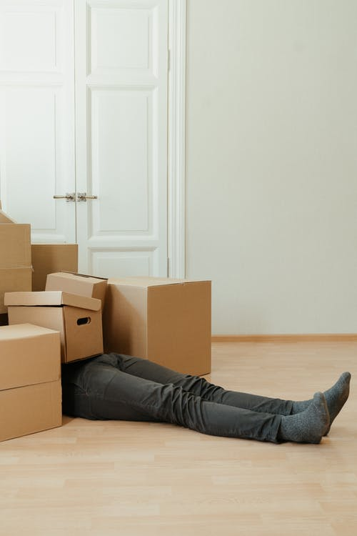 Person in Black Pants Lying on Brown Cardboard Box