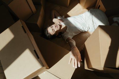 Woman in White Shirt Lying on Brown Cardboard Box