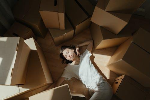 Woman in White Long Sleeve Shirt Lying on Brown Cardboard Box