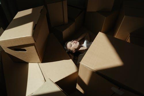 Baby in White Shirt Lying on Brown Cardboard Box