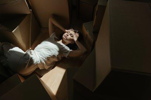 Woman in White T-shirt Lying on Brown Cardboard Box