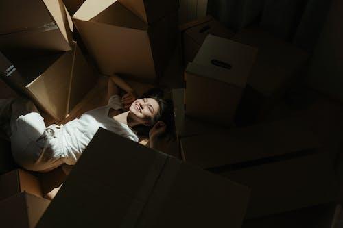 Man in White Dress Shirt Lying on Brown Cardboard Box