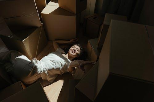 Girl in White Shirt Lying on Brown Cardboard Box
