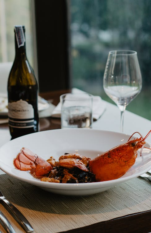 Delicious freshly boiled lobster with spices on white ceramic plate served with aromatic wine in fine dine restaurant