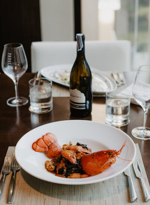 Delicious appetizer with boiled lobster and wine