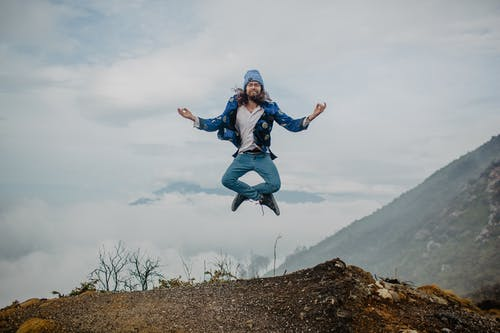 Man jumping on mountain plateau against cloudy sky
