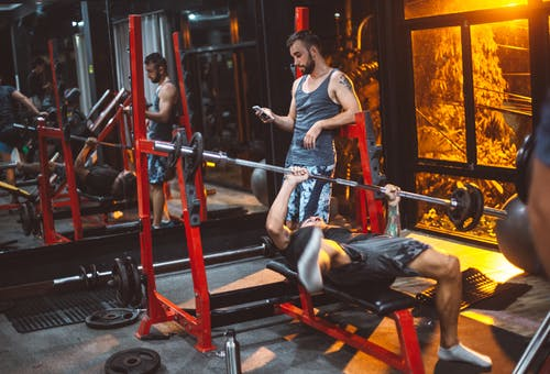 Sporty fitness trainer and man lifting barbell