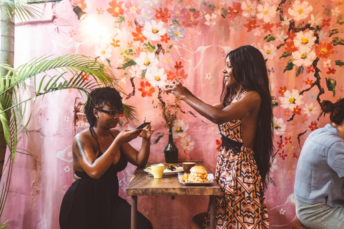 Side view happy African American females in stylish dresses taking photos on smartphones of freshly cooked food while having lunch in cozy cafe against painted wall