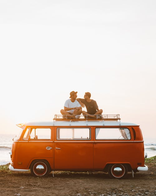 Silhouettes of full body faceless male friends in casual clothes resting on camper van roof and chatting in countryside in sunset time