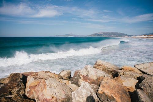 Waves running on rocky coast against blue sky