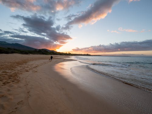 Sandy beach with waving ocean and cloudy sky at evening