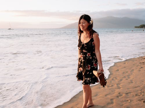 Woman in Black and White Floral Dress Standing on Beach