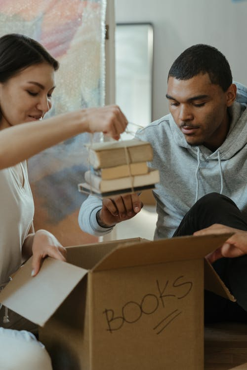 Man in Gray Crew Neck Shirt Holding Brown and White Box