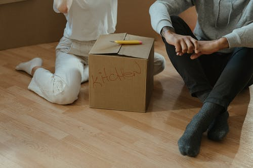 Person in White Long Sleeve Shirt and Black Pants Holding Brown Cardboard Box