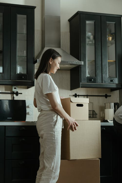 Woman in White T-shirt and Brown Pants Standing Beside Kitchen Sink