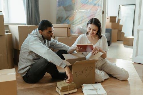 Man in Gray Dress Shirt Holding Brown Cardboard Box