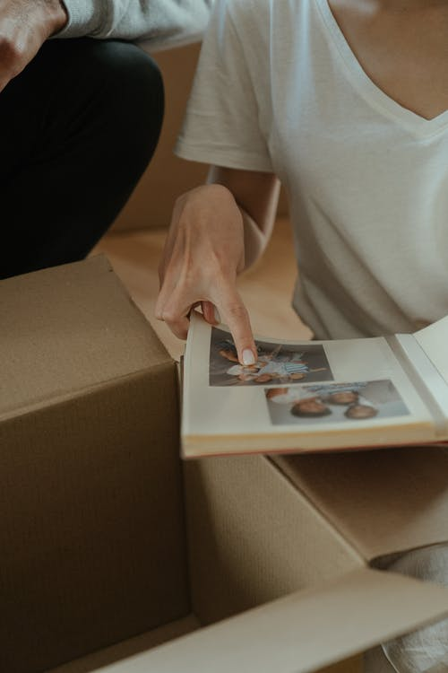 Person in White Shirt Holding White Printer Paper