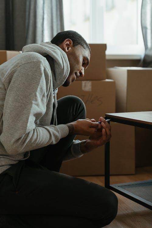 Man in Gray Hoodie Using Black Tablet Computer