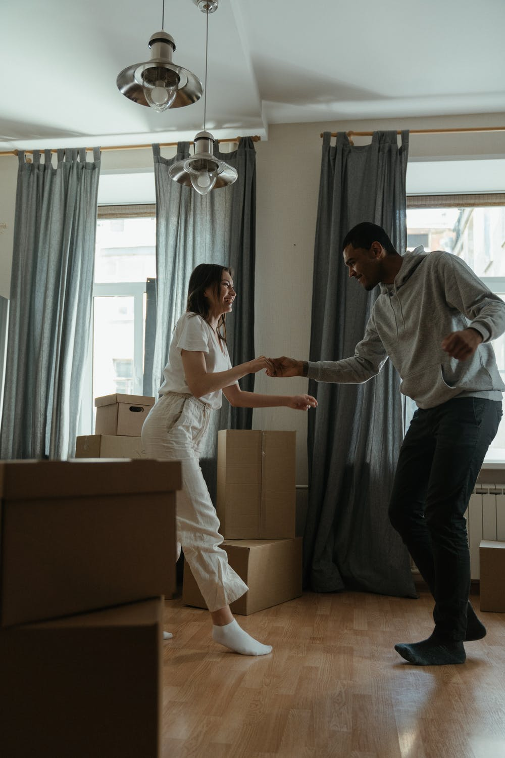 young couple dancing in their living room around boxes
