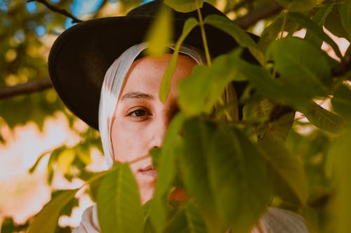 Selective focus of young female in hat and headscarf looking through foliage of tree at camera