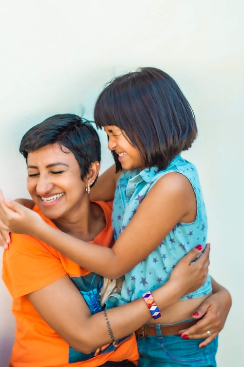 Positive young ethnic woman embracing cheerful little girl while having fun together  against white wall