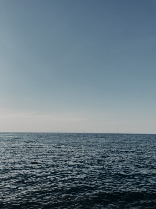 Picturesque seascape of blue rippling surface of endless sea under bright clear sky