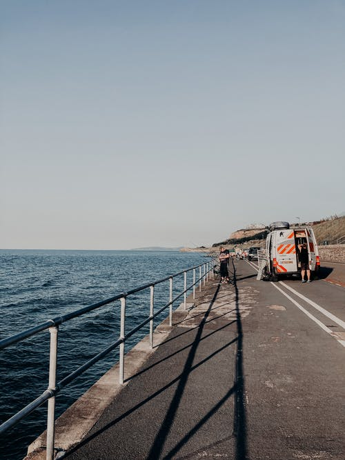 White and Red Van on Gray Concrete Road Near Sea