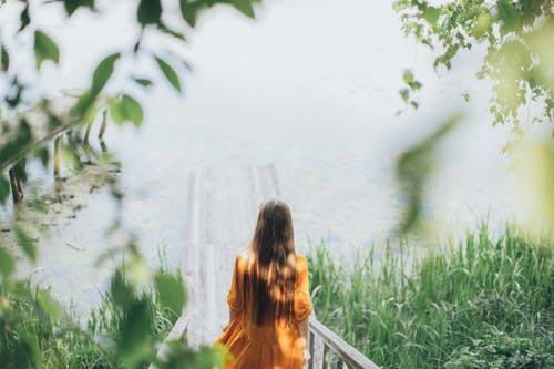 Young woman walking down on wooden path towards lake