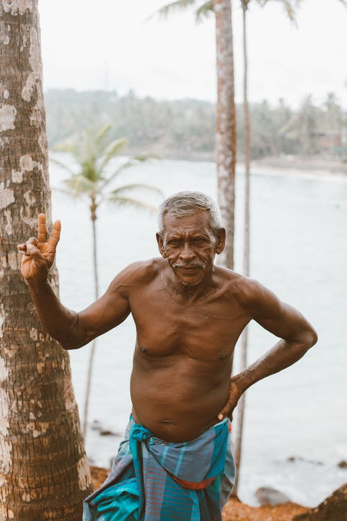 Ethnic old man standing on coast of river