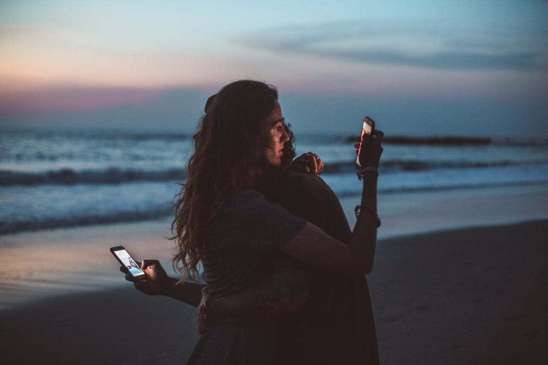 Couple hugging and using smartphone near sea on sunset