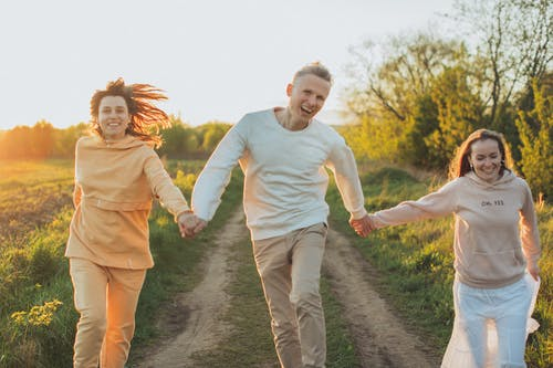 Happy friends running in pathway in rural field