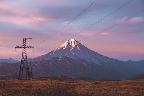 High voltage power lines against mountains in sunset