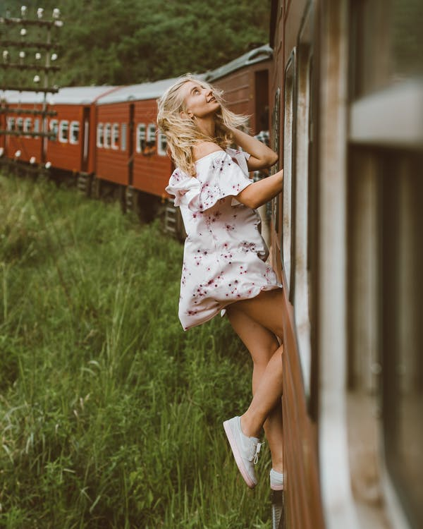 Side view of full body young woman in air dress leaning out from exit door and holding on to railroad while riding train past green grass