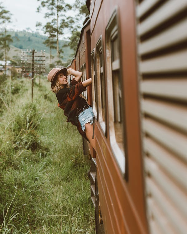 Young woman riding train leaning out of wagon