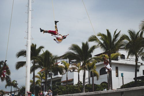 Male gymnasts hanging on ropes in city
