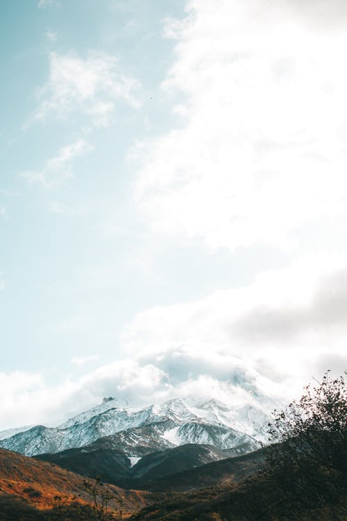 Picturesque mountains with peaks in snow and clouds