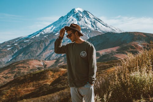 Young stylish man in hat and modern sunglasses standing on hill with hand in pocket against high snowy mountain