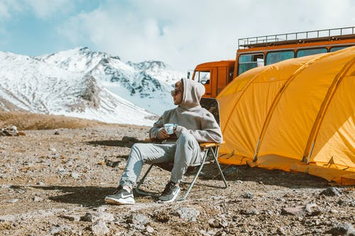 Man sitting near camping and looking at mountain view
