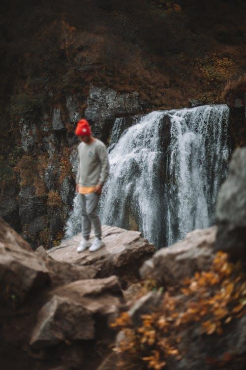 Male traveler on cliff near waterfall