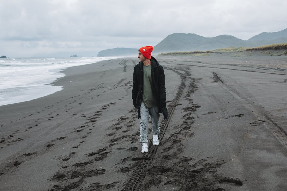 Male tourist walking along empty beach and admiring view on ocean