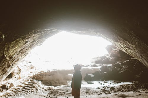 Side view of unrecognizable traveler standing in mountain cave in light of bright sun and admiring stone formation